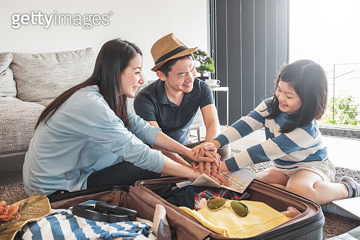 Asian family packing bag/luggage and planning to travel on summer vacation