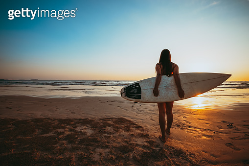 woman with surfboard on beach