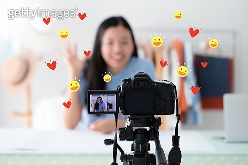 Beautiful asian woman blogger is talking in front of the camera to recording vlog video live streaming at home with heart and smile face icon.Business online influencer on social media concept.