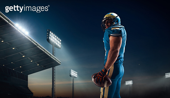American football player in professional sport stadium in night.