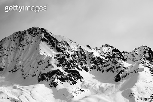 Black and white view on snow sunlight mountain and gray sky in evening