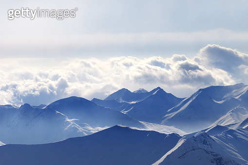 Silhouette of high snowy mountains in mist and sunlit cloudy sky at winter