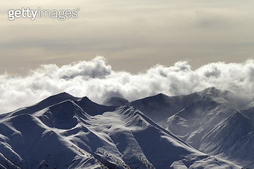 Snowy sunlit mountains in haze and cloudy sky at winter evening