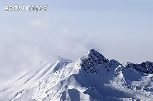 Snowy mountain peaks in haze