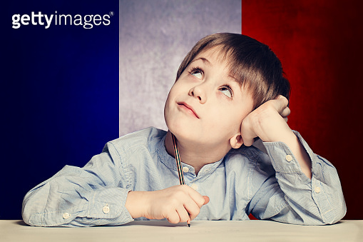 Learn french language concept. Happy child student with flag Fra