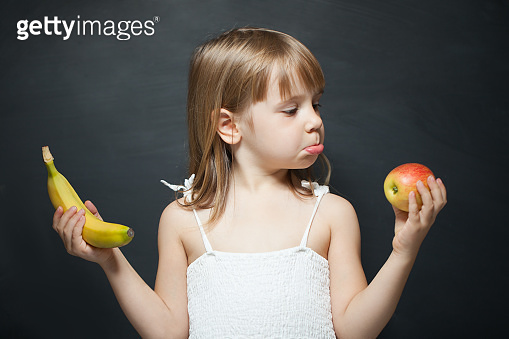 Little girl with apple and banan in the hands. The choice between fruits. Facial expression.