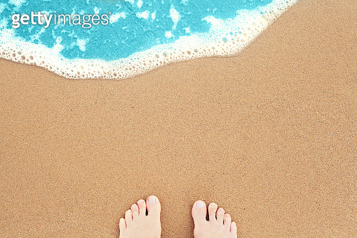 Feet on sea sand and surf. Vacation on ocean beach, summer holiday