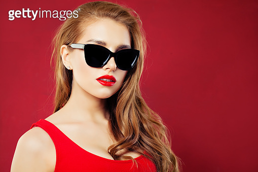 Woman in sunglasses. Fashion portrait of beautiful girl wearing sunglasses on red background