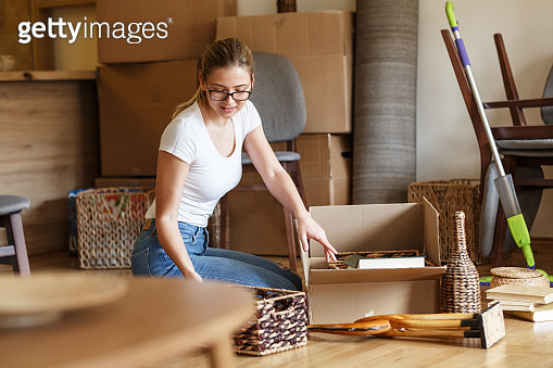 Young woman unpacking cardboard boxes at new home.