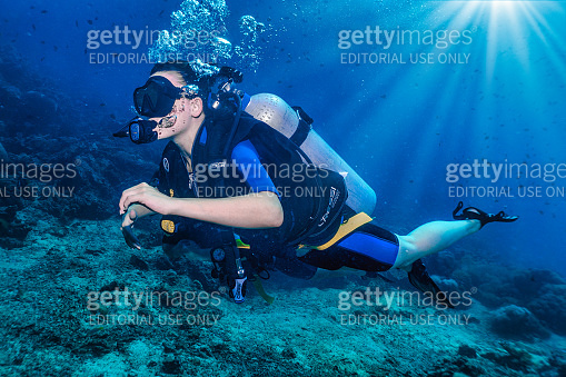 Environmentally friendly female eco tourist Scuba Diving on vacation over coral reef