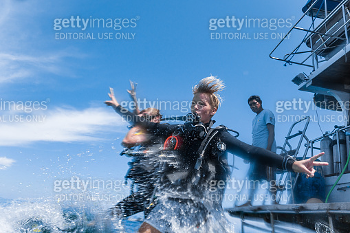 Scuba Diver friends jumping off boat with arms outstretched