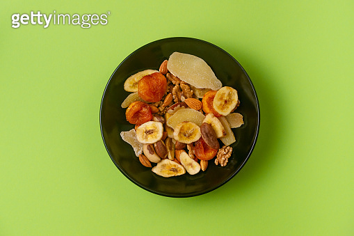 A fresh dried and candied fruits and nuts in black bowl on green bakground.