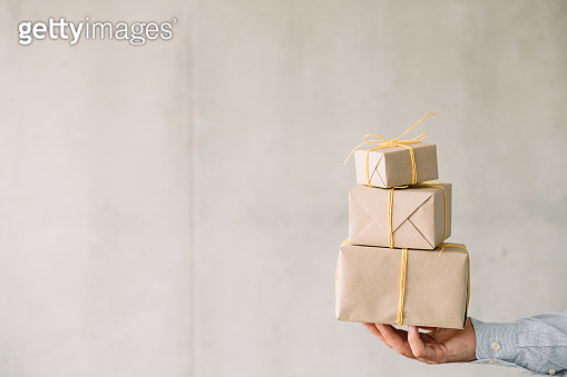 corporate birthday party beige gift boxes man hand