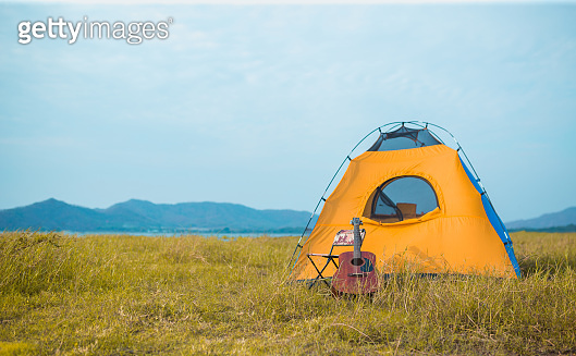 Camping tent,chair and guitar near river mountain at forest for travel.