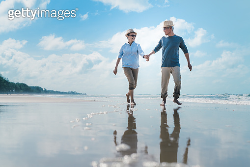 Asian couple senior elder retire resting relax walking running at sunset beach honeymoon family together happiness people lifestyle