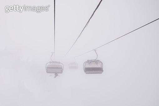 Empty ski lift in fog, foggy conditions. Cable car in the fog.Ski chairlift in a foggy and snowy mountains.