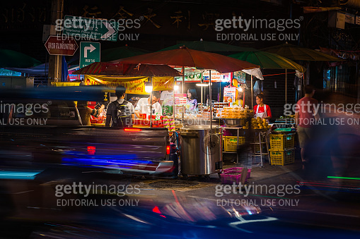 Bangkok family working night market stall beside busy road Thailand