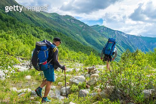 Trekking in mountains. Friends hike in mountain trail