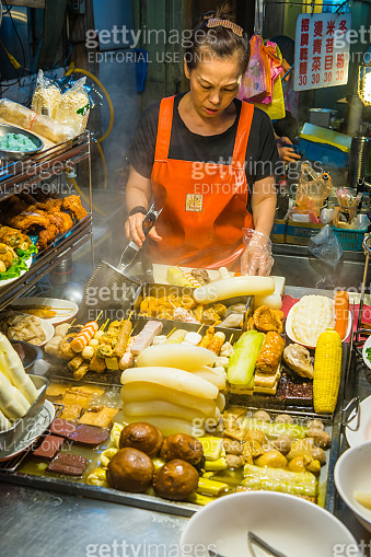 Woman cooking traditional food night market street stall Taipei Taiwan