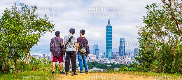 Young men overlooking Taipei 101 downtown skyscrapers from mountain Taiwan