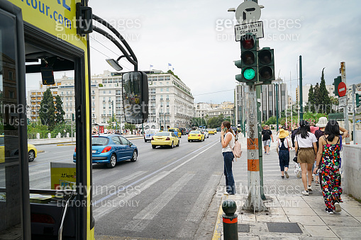 Woman waiting at pedestrian crossing talking on mobile phone.