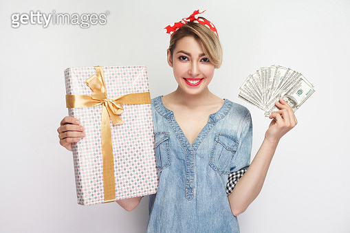 Portrait of beautiful young woman in casual blue denim shirt with makeup and red headband standing, showing gift box and fan dollars with toothy smile.