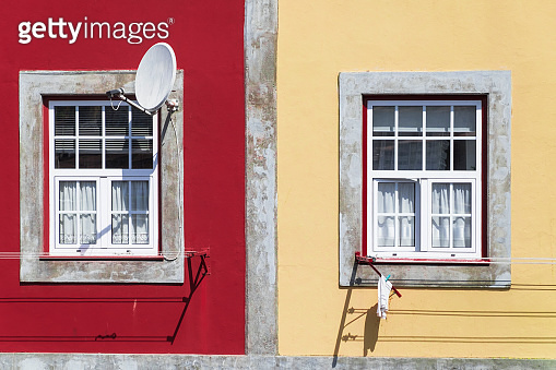 Satellite dish on the window. red and yellow walls with two windows.