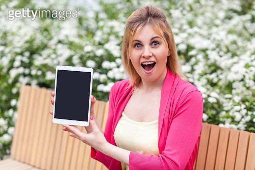 Portrait of shocked beautiful young businesswoman in casual style sitting in bench on park, showing tablet empty screen with unbelievable face, opened mouth and looking at camera.