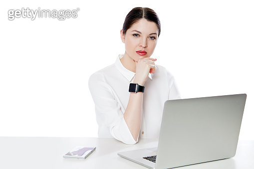 Portrait of serious successful brunette businesswoman in white shirt sitting with laptop, touhing her chin and looking at camera with thoughtful face.