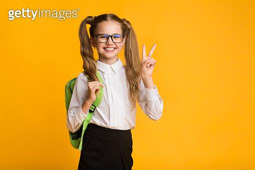 Smiling Schoolgirl Gesturing Victory Sign In Studio