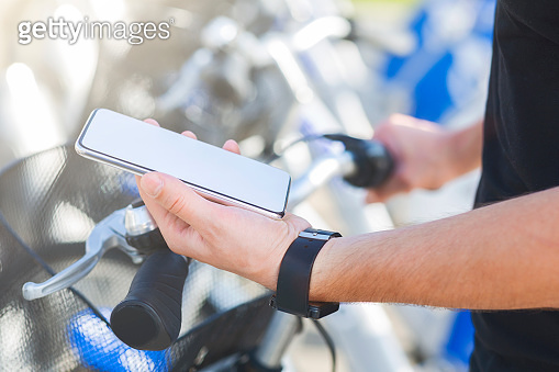 Cyclist texting on smartphone, riding on bicycle