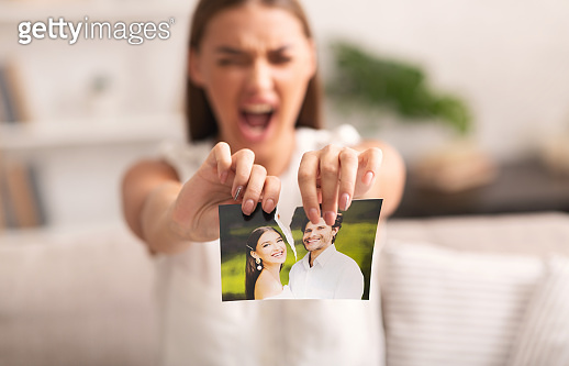 Angry Woman Ripping Photo With Ex-Husband Indoor