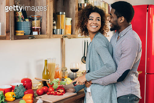 Young african-american couple preparing salad in kitchen