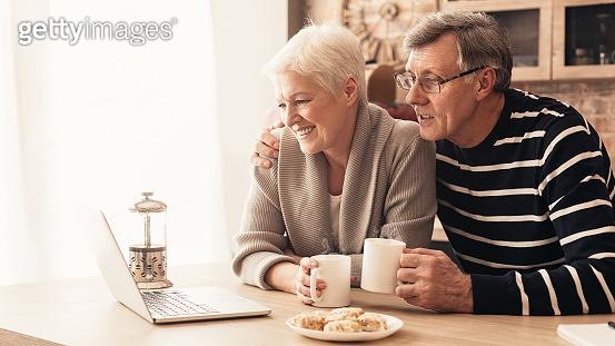 Elderly retired couple reading their social media news on laptop in kitchen