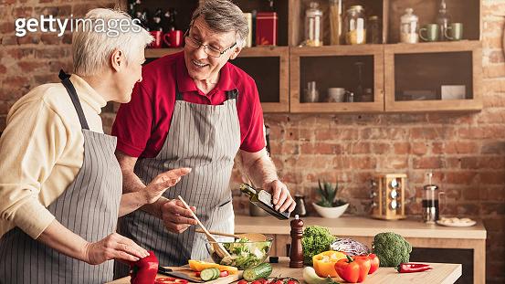 Laughing seniors cooking vegetable salad at kitchen