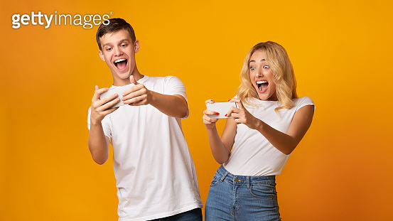 Excited young man and woman playing together on smartphones