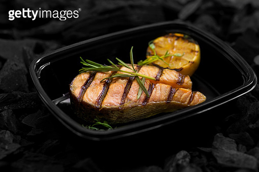 Close up of fresh cooked fish with rosemary in box
