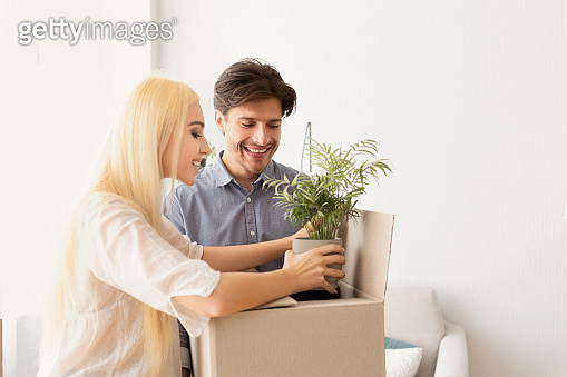 Gladful Couple Packing Plant In Moving Box, Copy Space