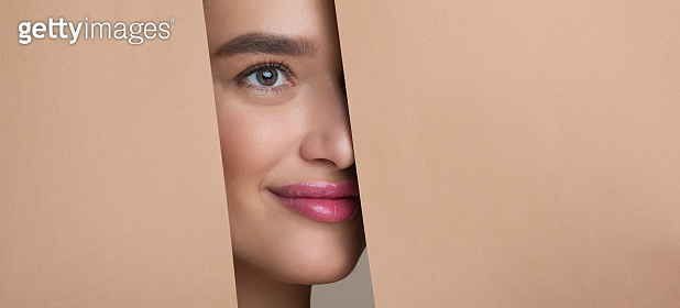Woman Peeking Out From Hole In Peach Paper
