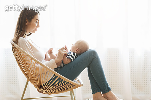 Mother with newborn baby on lap sitting in woven chair