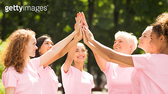 Breast Cancer Volunteer Group Of Multiethnic Women Giving High-Five Outdoor