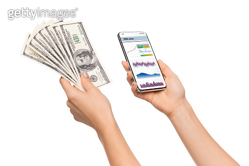 Trading app opened on smartphone and cash in female hands