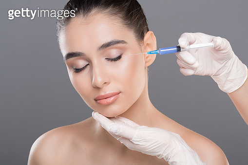 Young woman getting beauty injection with hyaluronic acid