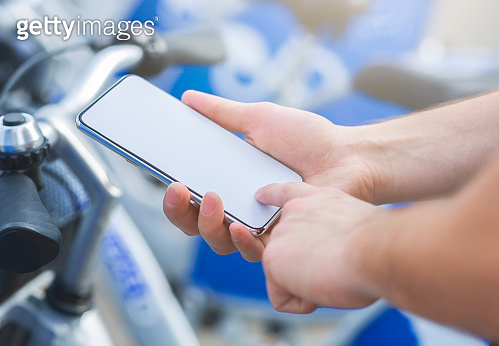 Man using cellphone, renting bicycle on mobile app