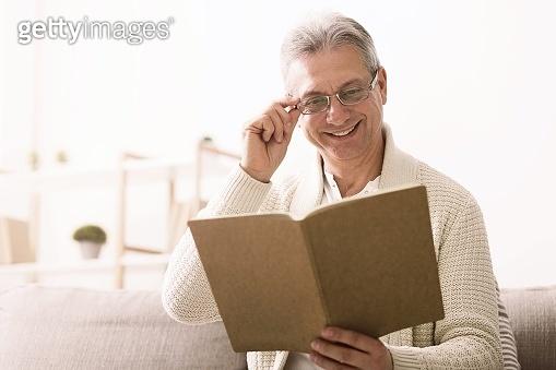 Mature man looking photos in album, having rest