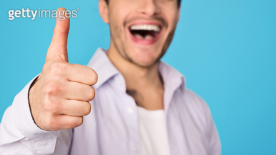 Pleased man showing thumb up and smiling