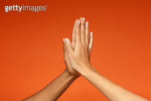 Man and woman greeting each other with high five