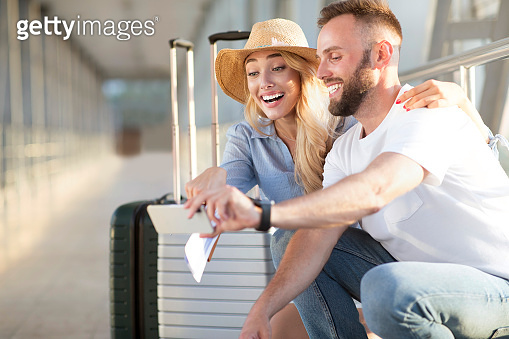 Excited couple in airport using smartphone, searching sightseeings