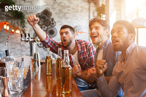 Diverse friends cheering for football team in sport bar
