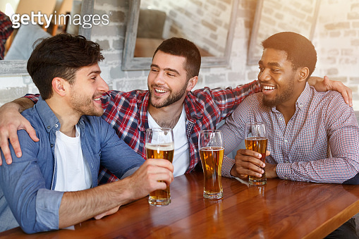 Best friends meeting and drinking beer in bar
